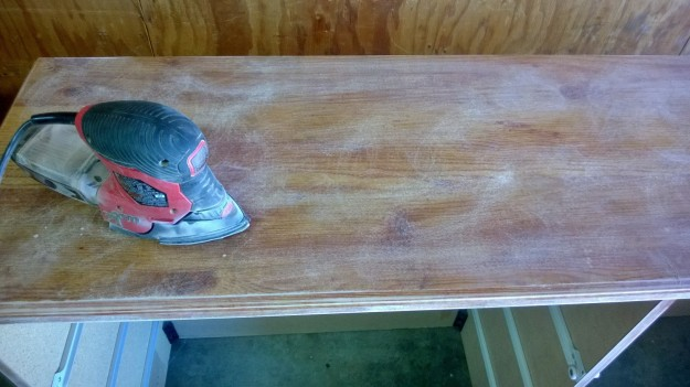 Sanding the top of the dresser with my electric  hand sander.